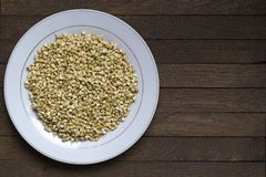 Sprouted buckwheat on white plate with copy space - Left position. White plate with Sprouted buckwheat inside on wooden table. Left position. Top view. Organic stock image