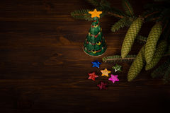 Spruce branch with cone and small Christmas tree on wooden planks Royalty Free Stock Image