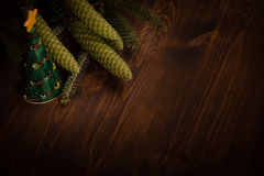 Spruce branch with cone and small Christmas tree on wooden planks Royalty Free Stock Photos