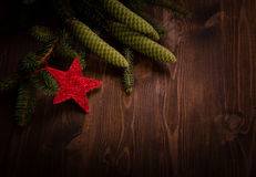 Spruce branch with cones and red star on wooden planks Stock Photography