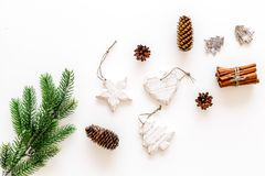 Spruce branch, cones and vintage toys in shape of spruce and stars on white background for decoration on chrismas or new. Year top view royalty free stock image