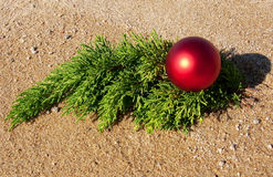Spruce branch and a New Year\'s ball on the sand Royalty Free Stock Image