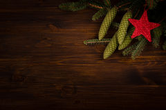 Spruce branch and red star on wooden planks Stock Images