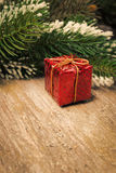 Spruce branch with snow, red gift box on vintage wooden table Stock Photography