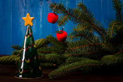 Spruce branch and tiny red apples and christmas tree Royalty Free Stock Photo