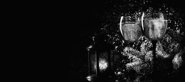 Spruce branches and champagne glasses on a dark background. Royalty Free Stock Photos