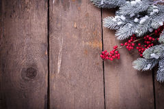 Spruce branches, decorative berries on aged wooden  background. Stock Image