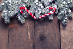 Spruce branches and decorative candy cane on aged wooden  backgr Stock Images