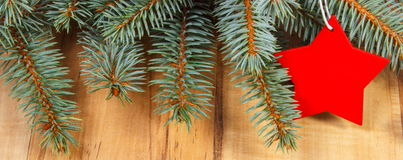 Spruce branches and red wooden star with copy space for text Royalty Free Stock Photo