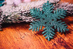 Spruce branches in the snow, and blue snowflake wooden background Stock Photography