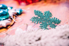 Spruce branches in the snow, and blue snowflake wooden background Royalty Free Stock Photography