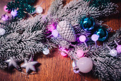 Spruce branches in the snow violet blue and white christmas balls on dark wooden background Royalty Free Stock Photos