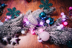 Spruce branches in the snow violet blue and white christmas balls on dark wooden background Stock Photo