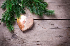 Spruce and decorative heart  on wooden background. Royalty Free Stock Photography