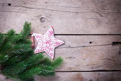 Spruce and decorative star  on wooden background. Royalty Free Stock Photo