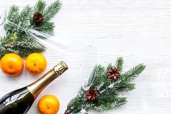 Spruce, mandarin, champagne bottle and glasses for christmas celebration on white background top view mockup Stock Images