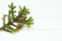Spruce twig with cones on white wooden background. New Year, Christmas. Toned image, film effect.  Stock Photography