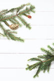 Spruce twig with cones on white wooden background. New Year, Christmas. Toned image, film effect.  Stock Images