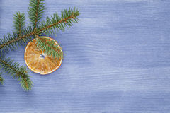 Spruce twig with dried orange slices on blue table Stock Photo