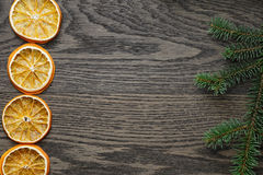 Spruce twig with dried orange slices on oak table Stock Photo