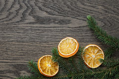 Spruce twig with dried orange slices on oak table Royalty Free Stock Image