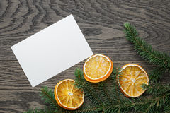 Spruce twig with dried orange slices on oak table Stock Image