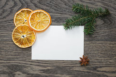 Spruce twig with dried orange slices on oak table Royalty Free Stock Images