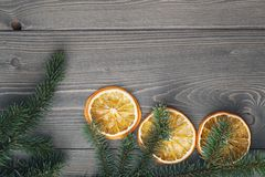 Spruce twig with dried orange slices on old table Royalty Free Stock Photo