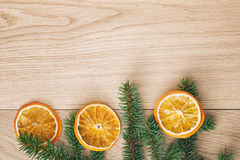 Spruce twig with dried orange slices on old table Royalty Free Stock Photography