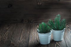 Spruce twigs in ceramic pail. On rustic wooden table with copy space, christmas decoration. Toned stock photos