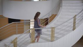 Spruced girl with hair iron is wound on up the marble stairs. Beauty wearing a designer dress made of synthetic fabric stock footage