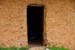 Sprucken gyttjahusvägg med den mörka dörröppningen Royaltyfri Fotografi