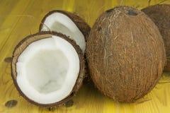 Sprucken kokosnöt på den gula trätabellen Förbereda den uppfriskande drinken för kokosnöt tropisk drink Tabellen på strandstången fotografering för bildbyråer