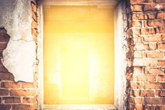 Sprucken tegelstenvägg med ljust gult ljus från ingången med effekt av ljus på slutet av tunnelen Arkivbild