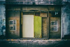 Sprucket fönster med slitna tabeller av kompenserat trä som rullgardiner Arkivfoto