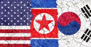 Spruckna sönderrivna USA-, söder- och Nordkoreaflaggor Arkivbild