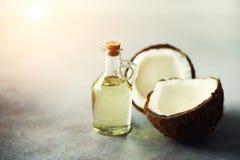 Spruckna två halvor av ny organisk kokosnöt och kokosnötolja på grå bakgrund kopiera avstånd Royaltyfria Bilder