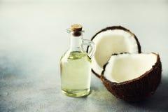 Spruckna två halvor av ny organisk kokosnöt och kokosnötolja på grå bakgrund kopiera avstånd Arkivbild