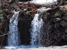 Sprudelnder Bach, der stromabwärts auf einem milden, sonnig, Vorfrühlingstag läuft Lizenzfreies Stockbild