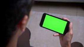 Spruit van de close-up de achtermening van mannelijke hand die een telefoon met het groene scherm binnen in flat houden stock videobeelden
