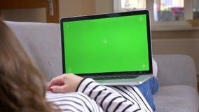 Spruit van de close-up de achtermening van vrouwelijke het letten op reclame op laptop met het groene scherm die op de laag binne stock video