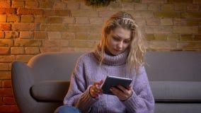 Spruit van de close-up de hoogste mening van volwassen Kaukasisch blondewijfje die de camera bekijken en tablet gebruiken die ter stock video
