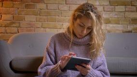 Spruit van de close-up de hoogste mening van volwassen Kaukasisch blondewijfje die de tablet gebruiken terwijl het zitten op de v stock videobeelden