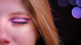Spruit van het close-up de halve gezicht van jong aantrekkelijk Kaukasisch wijfje dat met roze mooie make-up recht camera bekijkt stock video