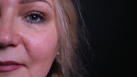 Spruit van het close-up de halve gezicht van oud Kaukasisch wijfje die die camera met achtergrond bekijken op zwarte wordt ge?sol stock videobeelden