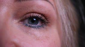 Spruit van het close-up de halve gezicht van oud Kaukasisch wijfje die met die ogen camera met achtergrond bekijken op zwarte wor stock video