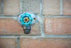 Sprundtapp för klappvatten på tegelstenväggen, ventil för blå gräsplan för aqua Arkivfoto