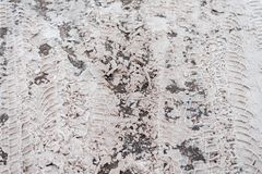Sprung snow on the road asphalt, white dirty snow traces of cars, a tread pattern on the road from trucks. In the city. Sprung snow on the road asphalt, white Royalty Free Stock Image