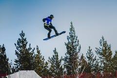 Sprungs- und Flugathletensnowboarder auf einem Hintergrund des blauen Himmels Stockbild