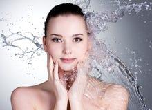 Spruzza dell'acqua sul fronte di bella donna Immagini Stock Libere da Diritti